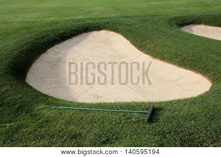Large sand trap on a well manicured fairway of a golf course.
