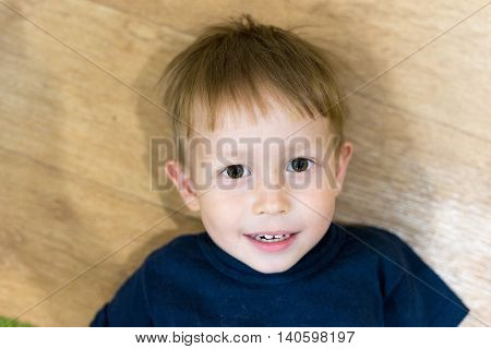 Little boy lying on the floor and looking into the camera. Looking with interest shaggy hairstyle.
