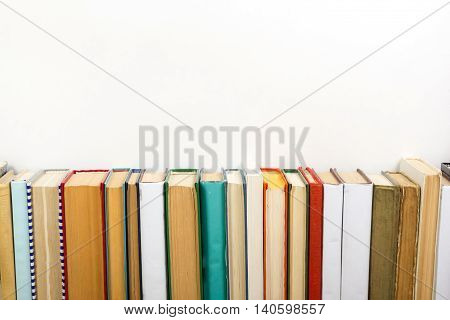 Colorful composition with vintage old hardback books, diary on wooden deck table and white background. Books stacking. Back to school. Copy Space. Education background
