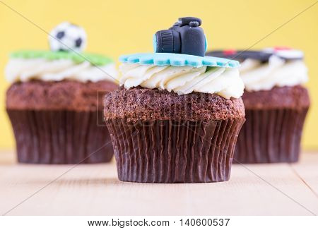 Delicious cupcakes with icons of ball tuxedo and camera on it on wooden desk and yellow background