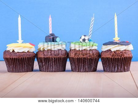 Delicious cupcakes with icons of ball tuxedo smiley and camera on it and candles on wooden desk and blue background