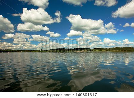 Karsinskie lake under blue sky with white clouds and with a beautiful reflection of clouds in water poland Bory Tucholskie. Horizontal view from water.