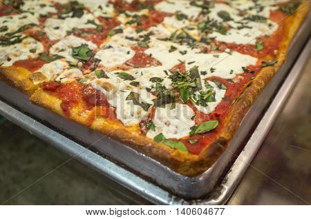 Large slices basil sauce and cheese pizza New York style