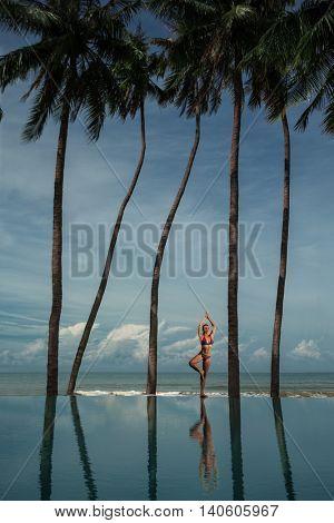 Yoga by woman on the beach near the ocean