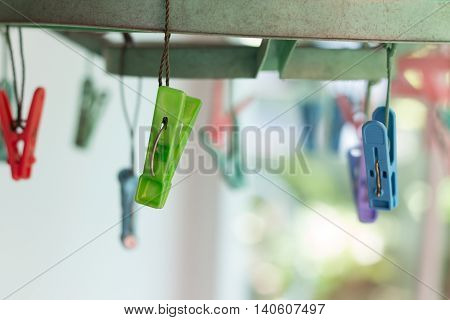 Clothes pegs or clothespins hang on a cord. Plastic clothes pegs on a washing line.(soft focus)