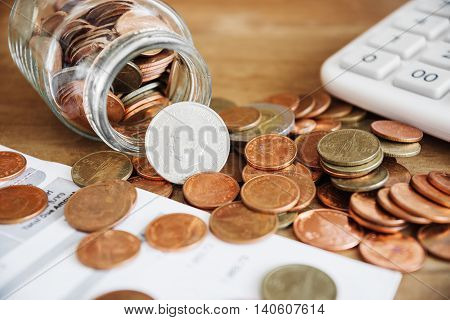 Coins spilling out of a glass bottle with bill and calculator Bill for income and expenditure and tax selective focus