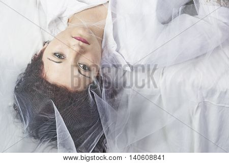 Young girl lying under a mesh fabric with a white background