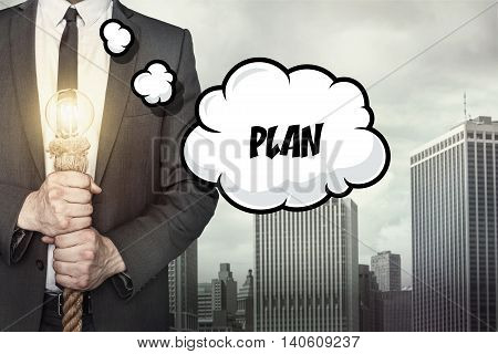 Plan text on speech bubble with businessman holding lamp on city background