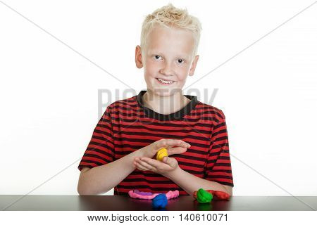 Happy Young Boy Playing With Modeling Clay