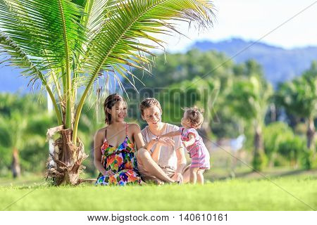 Young Family Spending Time In A Tropical Garden