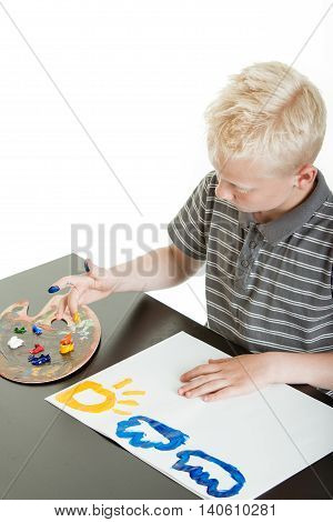 Little Boy Painting A Colorful Sun And Clouds