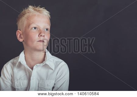 Pensive Young Boy Looking Upward Over Black