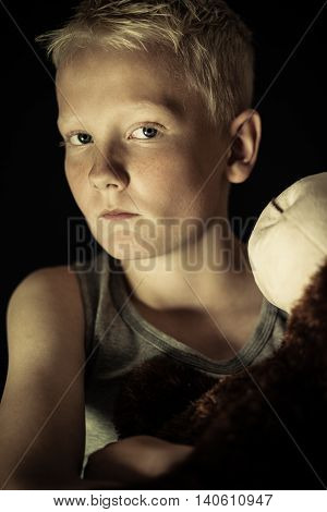Serious Little Boy In Dim Light Holding Toy