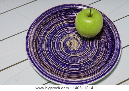Green apple on theblue pottery glazed plate. Ceramic plate with an apple on a blue wooden background.