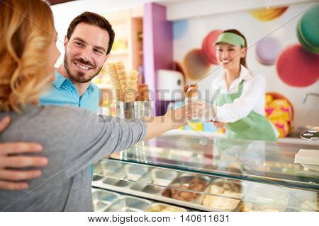 Smiling man buying ice cream his girl in pastry store