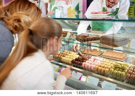 In pastry shop girl choose colorful macarons from showcase