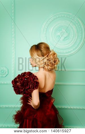 Sexy stylish blonde beautiful woman near green decorated wall. bouquet of red camellia flowers, pompons. Red dress.