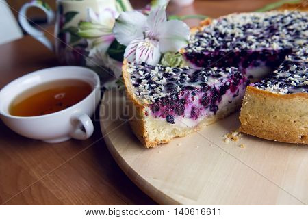 pie from fresh blueberries sprinkled with coconut and standing on a wooden stand, standing next to a porcelain teapot with white Cup tea with flowers