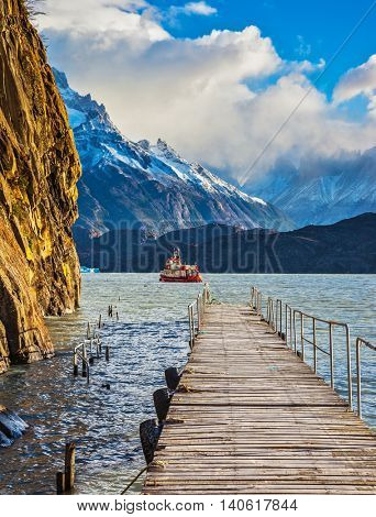 Pleasure boat for tourists swim with wooden pier. Grey Lake in the national park Torres del Paine, Chile