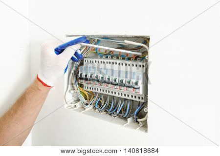 Electrician installing an electrical fuse box in a house.