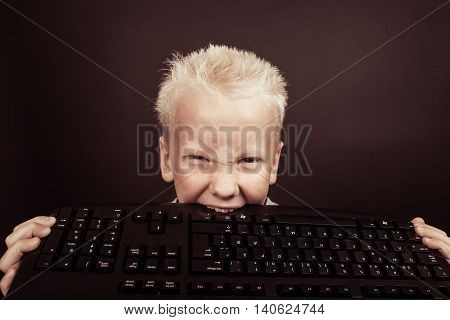 Furious Blond Boy Bites Into Black Keyboard
