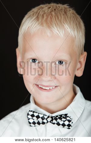 Smiling Blond Boy Wearing Checkered Bow Tie