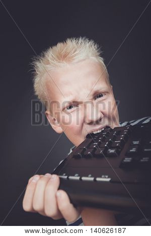 Angry Boy With Blond Hair Holding Keyboard