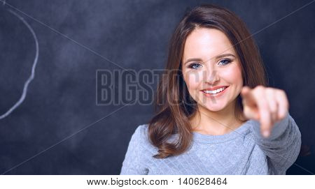 Young cute smiling girl pointing on you isolated on gray backgrund.