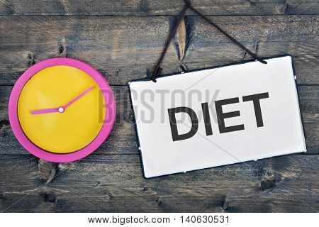 Diet sign and clock on wooden table