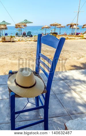 Straw hat on blue woden chair near sea beach