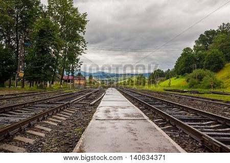 Railroad near the mountains at the cloudy day.