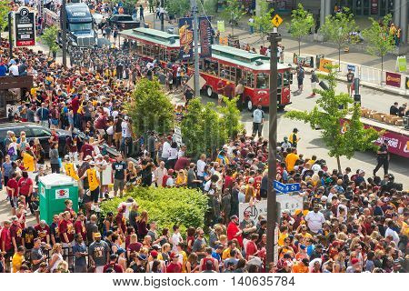 CLEVELAND OH - JUNE 22 2016: Crowds jam the streets at the start of the Cleveland Cavaliers' NBA championship parade with participants on board Lolly the Trolley and on the sidewalk.
