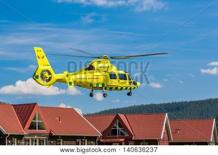 Klövsjö, Jämtland, Sweden - July 25, 2016: Ambulance helicopter close to houses after take off. Ambulance helicopter after take off close to houses.