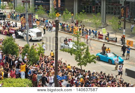 CLEVELAND OH - JUNE 22 2016: Imam Shumpert of the Cleveland Cavaliers (in turquoise car at right) is cheered by the crowds in the Cavs' NBA championship parade.