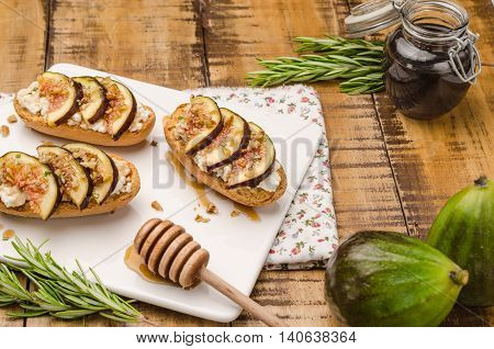 Swedish toasts with figs cheese rosemary honey and walnuts on a cutting board