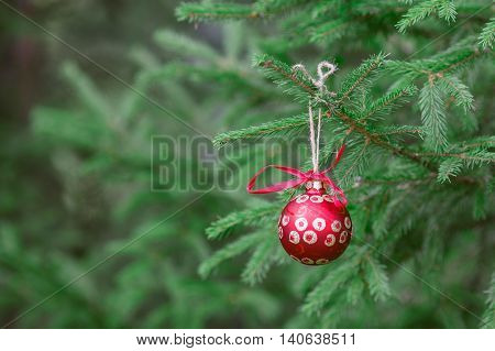Decorating Christmas tree with one red ball