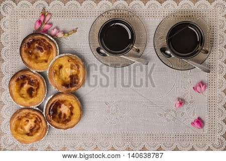 Pastel de nata typical Portuguese egg tart pastries and black coffee on a set table. Top view with copy space