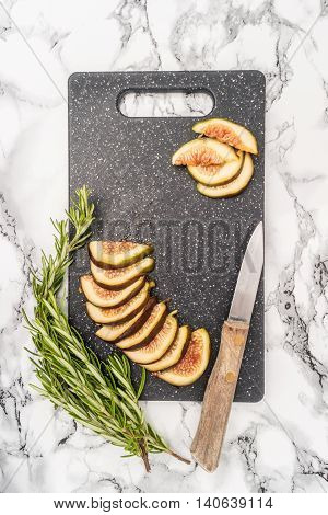 Fresh sliced figs rosemary and knife on cutting board. Top view