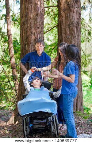 Family standing in woods giving tube feeding to disabled boy in wheelchair