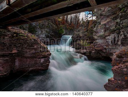 Saint Mary Falls Long Exposure rushes underneath footbridge