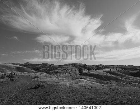 Clouds shoot across the sky in a Black and White scene at the Painted Hills of Oregon.