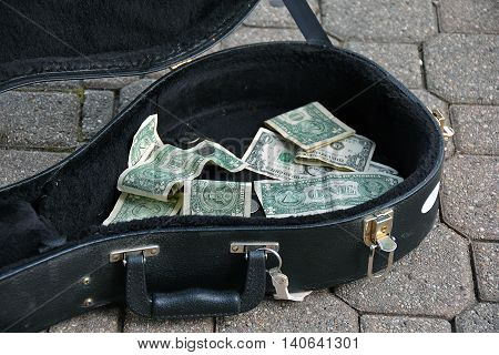 Loose dollar bills in a black guitar case.