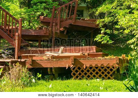 An old dilapidated backyard deck in the process of being dismantled and removed