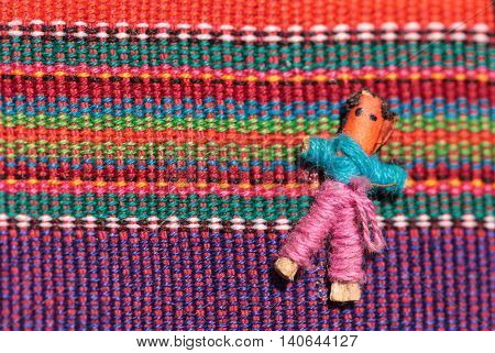 Macro of a handmade little textured Mexican cloth doll in multiple colored fabric.