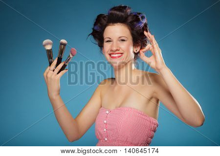 Cosmetic beauty procedures and makeover concept. Woman in hair rollers holding makeup brushes set making ok sign gesture on blue