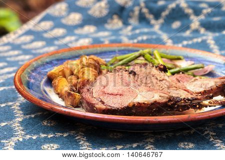 Rack of lamb with roasted golden baby potatoes seasoned with rosemary and sea salt and garnished with asparagus, onions and mushrooms on a dinner plate. A royal blue tablecloth is spread under the place setting.