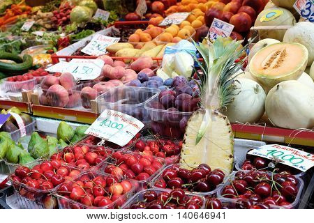 fruit stand in street market with pineapple cut