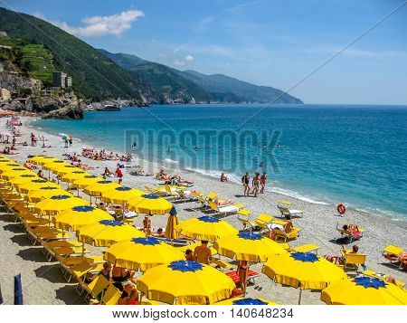 Monterosso al Mare, Ligurian Coast, Italy - June 4, 2010: colorful beach umbrella at the Monterosso beach in Cinque Terre National Park.