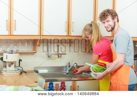 Young couple cooking together washing fresh vegetables red pepper green lettuce in kitchen under water stream preparation salad vegetarian meal