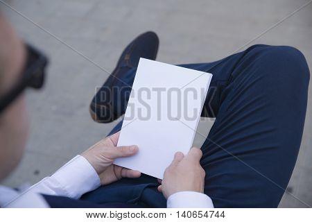 Mockup cover magazine, catalog, book. Man reading a blank magazine, catalog, book on the bench.